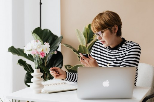 busy lady talking on smartphone and writing in notebook while working remotely at home